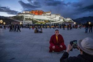 A Tibetan Buddhist monk has his photo taken in front of the Potala Palace
