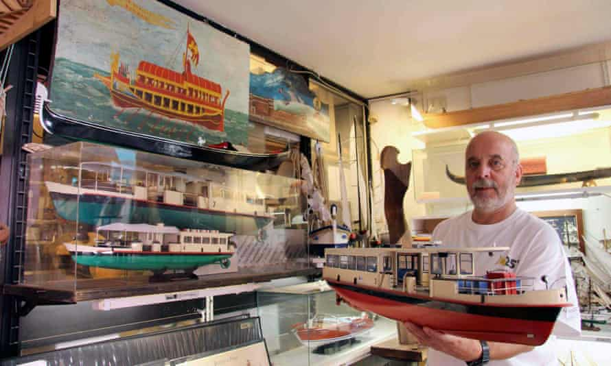 Interior of Gilberto Penzo's shop in Venice, Italy, with Penzo in shot, holding a model boat.