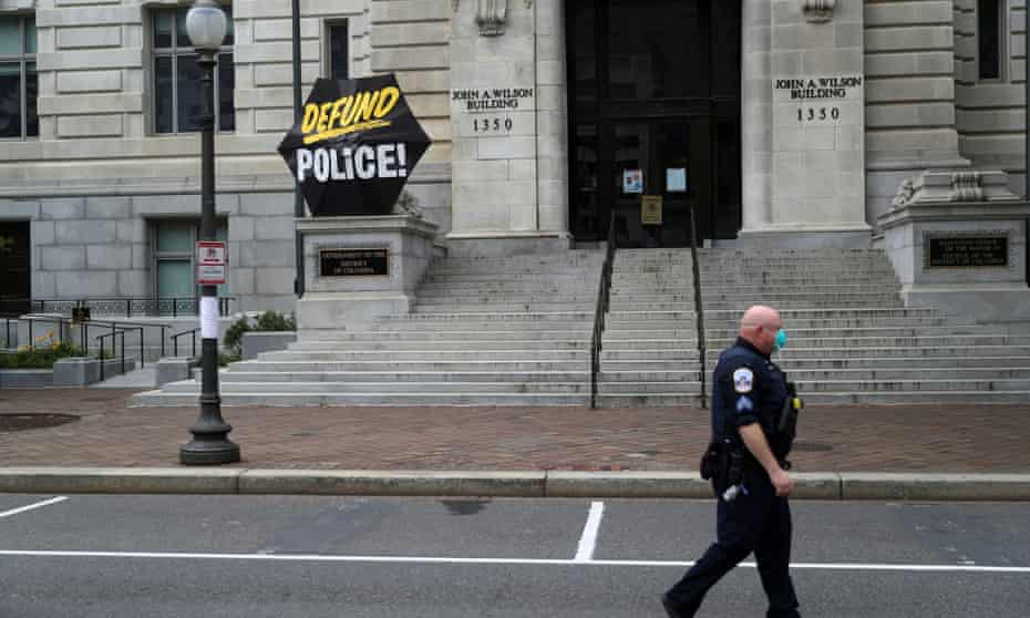 A Washington DC police officer walks past an umbrella reading 'Defund Police' on the steps of a city government building, 19 June 2020.