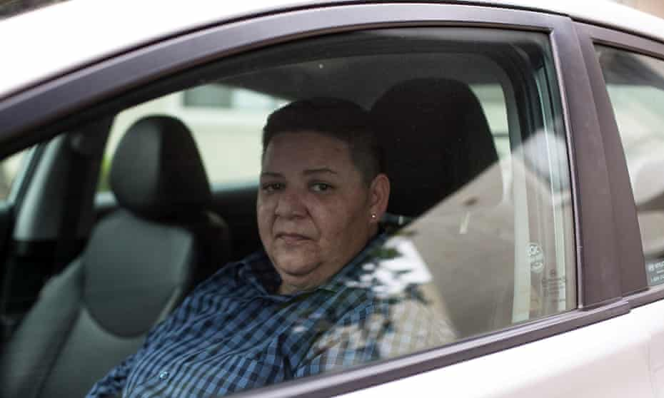 Rebecca Graham, who has stopped working for Uber, sits in her car that she uses to drive for competitor Lyft.