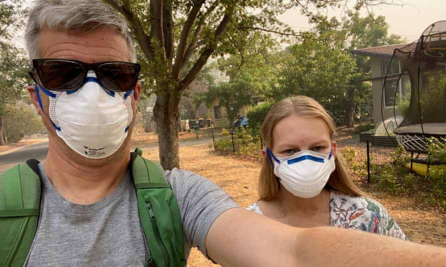 Shaun Humphreys and Lilia Boag Humphreys walk to the shops in smoke-filled Canberra in December 2019