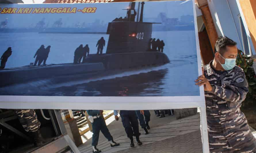 Military personnel moving a photograph of the submarine.