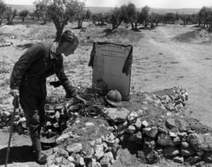 An officer of the International Brigades lays twigs on the mass grave of soldiers who died fighting in the civil war, circa 1937.
