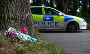 Flowers left at the roadside with a police car in the background.