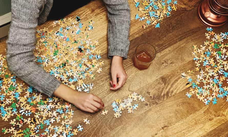 Someone puts a jigsaw puzzle together