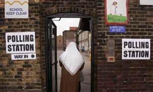 woman in headscarf going into polling station at school
