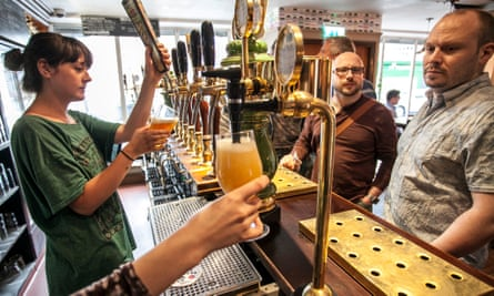 barmaid pouring craft beer as blokes wait