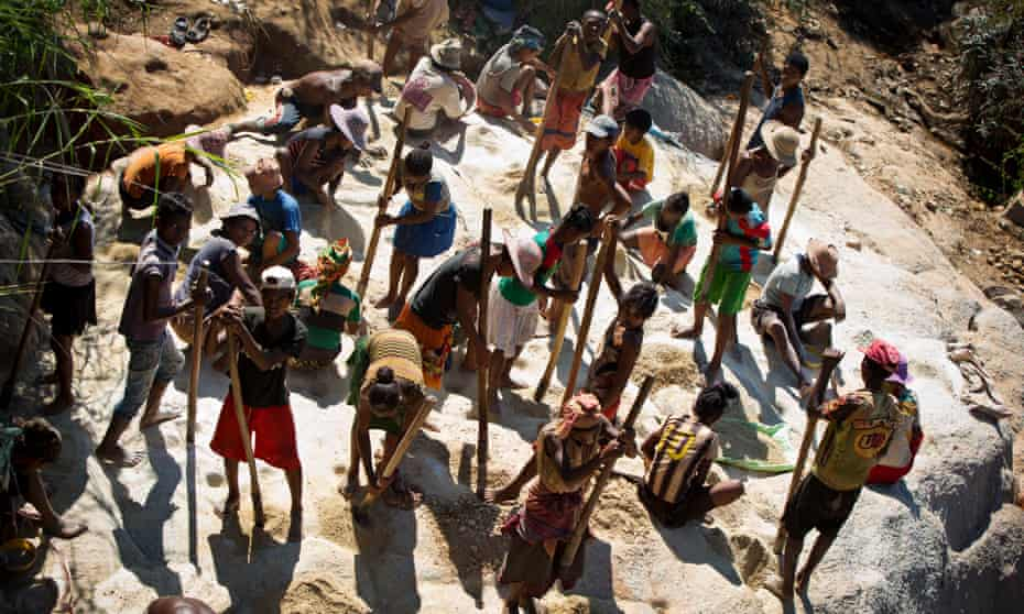 Women and children pound stones to find gold ore in Madagascar, April 2016.