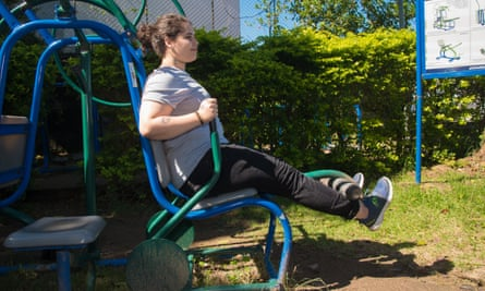 A woman works at an outdoor gym.