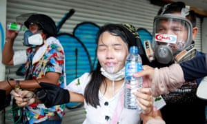 A demonstrator gets assistance as she seemingly reacts to being affected by tear gas on Friday.