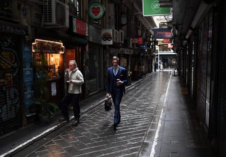 People walk through a small deserted laneway usually packed with open cafes and people during their lunchtime in Melbourne.