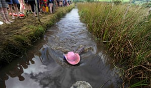 A swimmer wearing a pink cowboy hat swims through the water