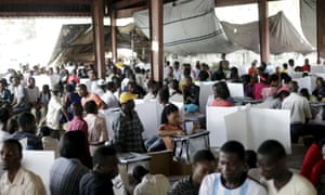 People gather to cast their votes at a polling station in a market in Port-au-Prince, Haiti