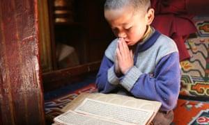 A Buddhist child prays in his Tibetan home.