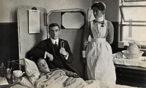 Dr Basil Hood sits by the bedside of a patient as a nurse watches on.