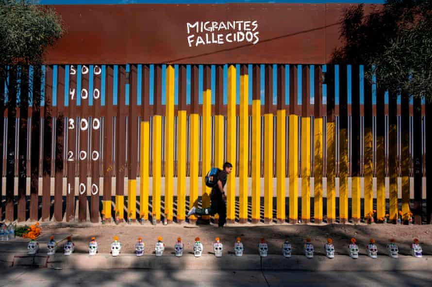 Junior Hernandez, from Guatemala, runs next to a section of border fence where a chart has been painted counting migrant deaths, in Tijuana, Baja California