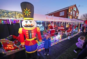 A boy stands outside a house belonging to Stan Yanetta, 58, in South Tyneside. Yanetta has spent three weeks adorning the property with festive lights and decorations for local children to enjoy