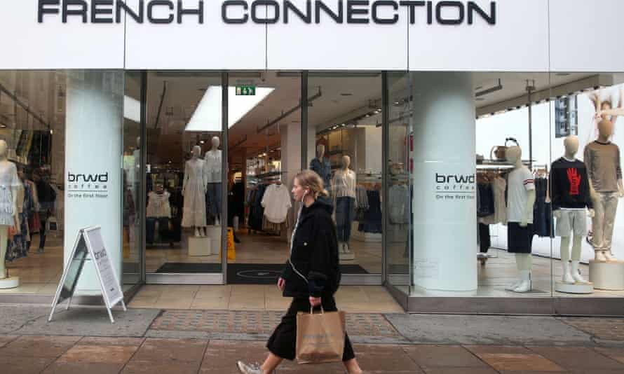 A woman walks past a French Connection store