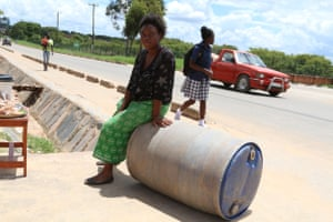 Loveness Chama, 19, of N'gombe township in Lusaka City, Zambia, rolling home a 210-litre drum of water
