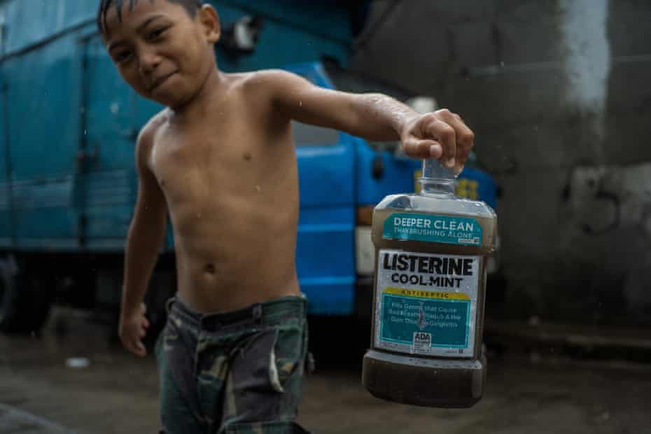 A boy plays with an old Listerine plastic bottle.