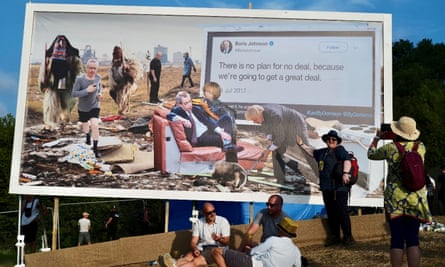 Festival-goers sit under an anti-Brexit billboard, a collaboration by Cold War Steve and Led By Donkeys.