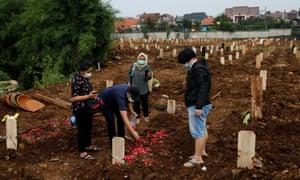 Pelayat Coki Pratomo meletakkan kelopak bunga di makam ibunya, Lolly Dumora Sari Siregar, 68 tahun, di pemakaman Jakarta untuk para korban virus corona di Indonesia.