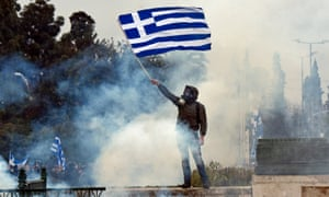 A man holds a Greek flag in a cloud of teargas.