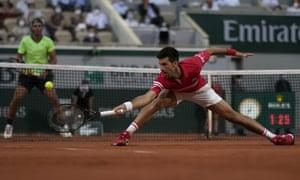 Novak Djokovic stretches to return the ball to Rafael Nadal.