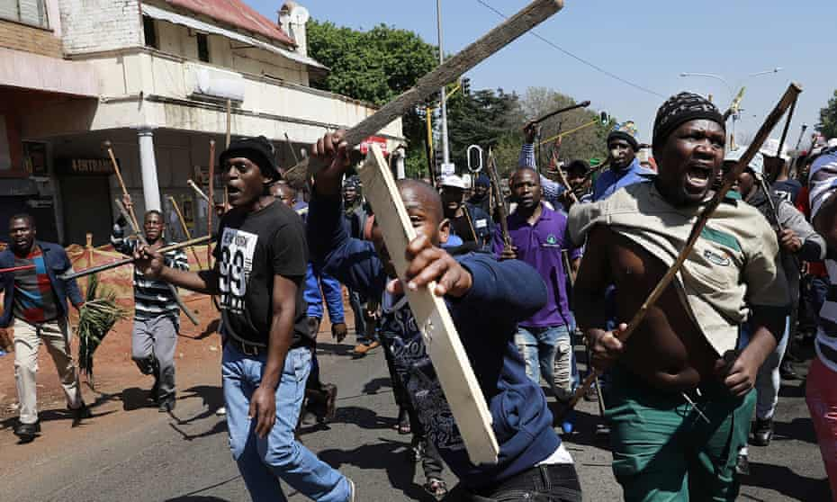 Men with homemade weapons march along a street i Johannesburg on Sunday.