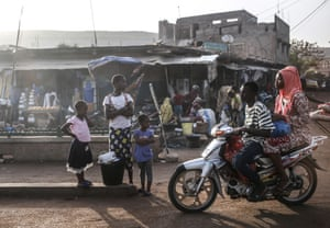 Bamako, Mali. People ride a motorbike through capital city