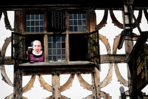 A woman wearing a Shakespeare mask toasts the Bard from a window of the Garrick Inn in Stratford