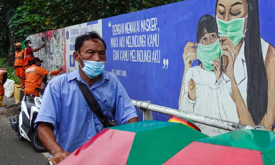 A man wearing pushes a cart past a mural in Jakarta encouraging wearing masks, as Indonesia relaxes its coronavirus curbs.