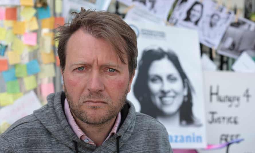 Richard Ratcliffe with photograph of Nazanin behind him