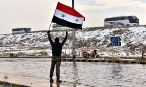 A man waves a Syrian national flag to a convoy carrying the last rebel fighters out of Aleppo.