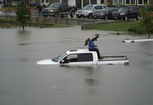 A man sits on top of a truck on a flooded road, Thursday in Houston.