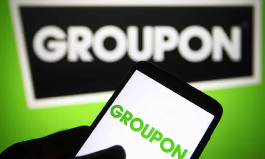 A Groupon logo is seen on a smartphone and a PC screen.