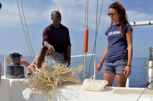 TV presenter Patrick Aryee and Marta Fernández, deckhand, watching a fishing line found on the water.