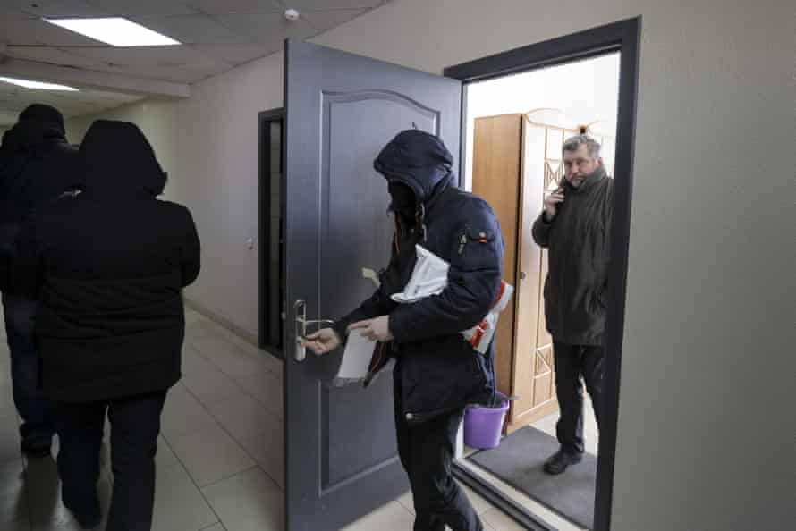 Police taking papers and computers from the Belarusian Association of Journalists' office as Andrei Bastunets, right, head of the BAJ, stands at the door.