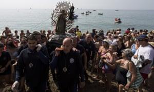 Penitents take part in the Virgen del Carmen brotherhood procession in Málaga, Spain