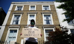 A protester wearing a face mask displays a message that reads: 'Where was your sacrifice?' near the home of Dominic Cummings, Boris Johnson's chief aide