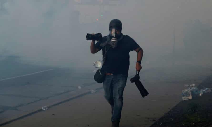 A photographer runs amid teargas in Minneapolis, Minnesota, on 30 May.