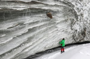 A person stands beside the glacier