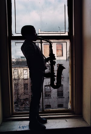 Young boy playing a saxophone in a window