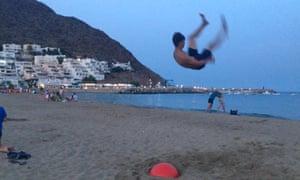 A boy performs a somersault on the beach at San José, Almeria, Spain, at dusk.