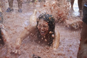 A woman falls into a puddle of squashed tomatoes at La Tomatina in Spain