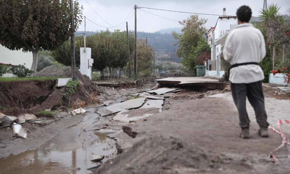 A man looks at a destroyed road after heavy rain in Evia, Greece.