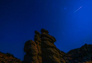 A photo taken with a long exposure shows meteor streaks crossing the night sky over the stone dolls in Kuklice, Macedonia