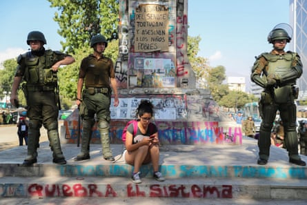 A woman uses her phone as security forces members look on in Santiago, Chile, on 16 December 2019.