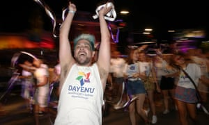A man throws up his arms with delight at the Sydney Gay and Lesbian Mardi Gras
