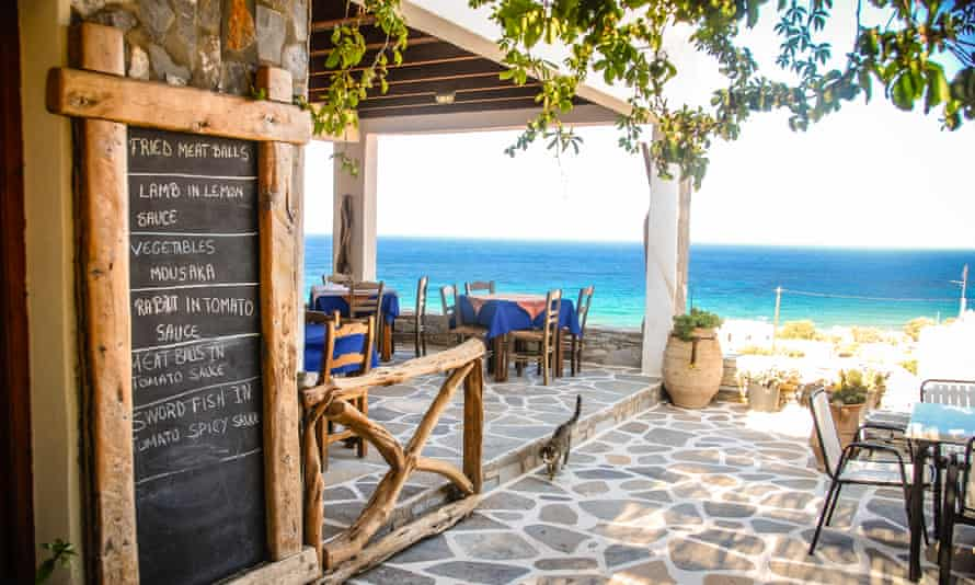 Greek taverna with a view to the sea and a chalk menu-board outside
